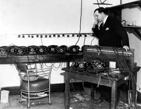 Capt. Thomas Duffy is seen with telephone equipment used to relay race information for handbooks from the Blum Building at 624 South Michigan Avenue. Photo printed on Dec. 6, 1941.