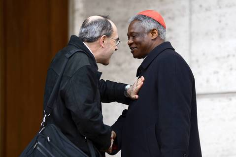Cardinal Peter Turkson, right, is greeted by French Cardinal Philippe Barbarin as he arrives for the final congregation before cardinals enter the conclave. Turkson is regarded as top African contender to be pope.