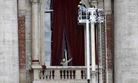Workers put up a red curtain on the central balcony, called the Loggia of the Blessings, of Saint Peter's Basilica at the Vatican.