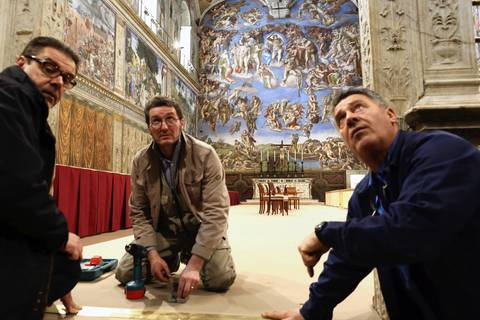Workers set up the Sistine Chapel where the papal conclave takes place.
