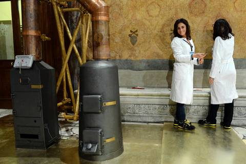 Two women working on the Sistine Chapel watch the proceedings near the stoves that will eventually send up white smoke signals announcing the election of the new pope.