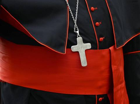 A cross rests on a cardinal's cassock as he arrives for a meeting in the Synod Hall at the Vatican.