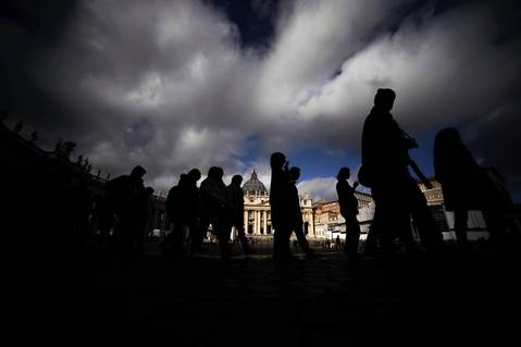 People walk in front of St. Peter's Basilica at the Vatican. The Vatican installed a special chimney on the Sistine Chapel from which white smoke will signal the election of a new pope as cardinals prepare for the historic vote next week after Benedict XVI's resignation.