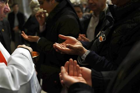 People receive communion while attending the Pro Eligendo Romano Pontifice Mass at St. Peter's Basilica, after which Cardinals will enter the conclave to decide who will be the next pope.