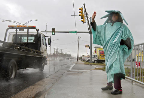 Erica Faltz braves the elements to wave to motorists on Jefferson Avenue as storms drenched the area on Tuesday morning. Faltz has worked as a waver for Liberty Tax Service since February.