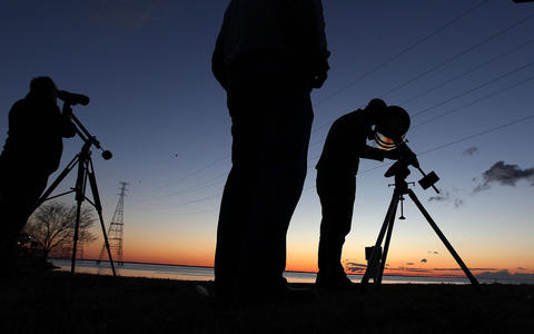 Jason Tackett (right) uses a reflector telescope as he and other star-gazers look for the comet Panstarrs Tuesday evening at Huntington Beach. The comet can be seen this week in the western sky in the vacinity of the moon.