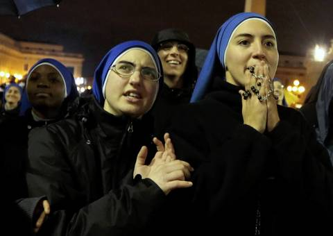 Nuns react as black smoke rises from the chimney above the Sistine Chapel, indicating that no decision has been made after the first day of voting for the election of a new pope, in the Vatican City.