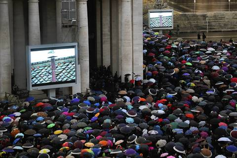 People gather around television screens in St. Peters Square displaying footage of the chimney on the roof of the Sistine Chapel as people wait for a signal that the Cardinals have elected a new pope.