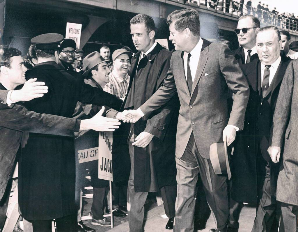Eager hands reach toward President John F. Kennedy as he walks from the O'Hare International Airport terminal building with Mayor Daley, right, on March 23, 1963. Approximately 5,000 people gathered at the airport to catch a glimpse of the president. A secret service agent is at Kennedy's right.