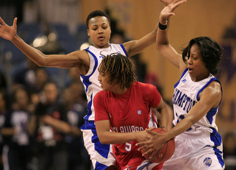 Delaware State's Tasia Bristow looks to pass around Hampton's Alyssa Bennett and Ariel Phelps during the first half of Wednesday's MEAC Tournament quarterfinal game.