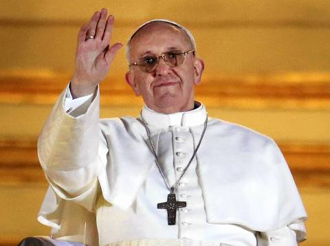 Newly elected Pope Francis waves to the waiting crowd from the central balcony of St. Peter's Basilica.