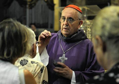 Argentine Archbishop Jorge Bergoglio places crosses on the faithful during a mass for Ash Wednesday in February 2013.