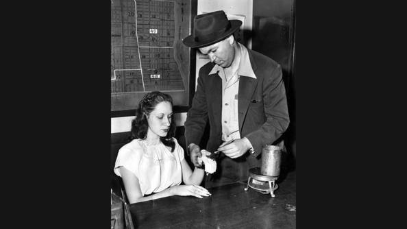 Ruth Steinhagen, 19, held in the shooting of Eddie Waitkus, has her hand coated with paraffin in a test for gunpowder marks, by Detective James Johnston at Summerdale police station on Chicago's North Side