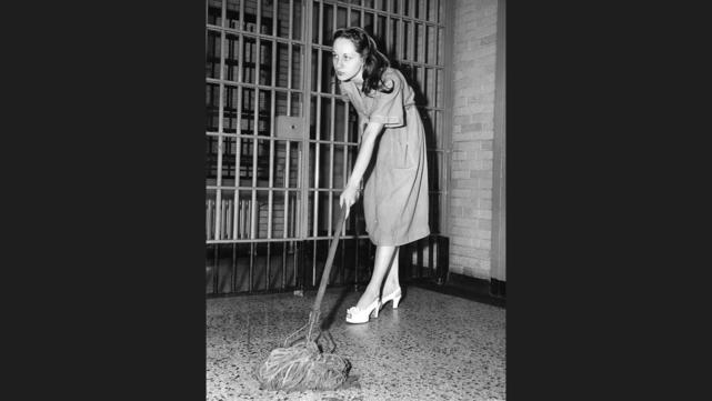 """Ruth Steinhagen """"mops"""" the floor of a cell in Cook County Jail, where she was being held in the shooting of baseball star Eddie Waitkus. The photo is staged for news cameras, because the mop and floor are dry."""