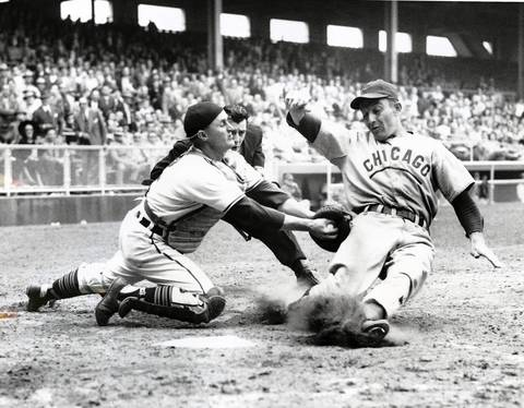 Chicago Cub first baseman Eddie Waitkus is tagged out by Cleveland catcher Joe Tipton at an exhibition game in Los Angeles.