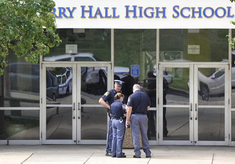 Baltimore County police confer outside Perry Hall High School a day after a shooting that took place in the school cafeteria.
