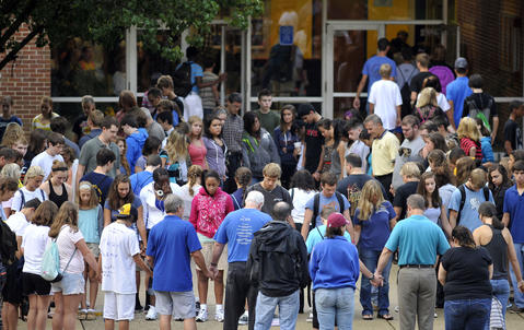 Students, family members and others gather to pray as students return for the second day of classes at Perry Hall High School.
