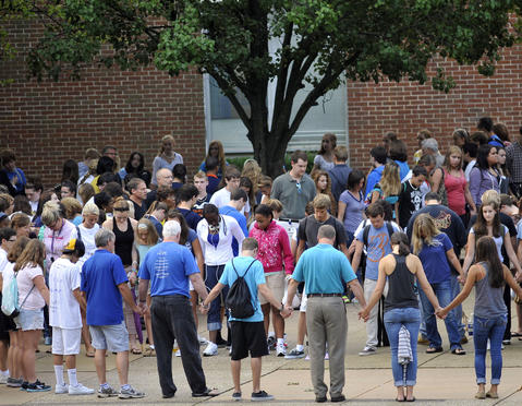 People gather to pray as students return for the second day of classes at Perry Hall High School.