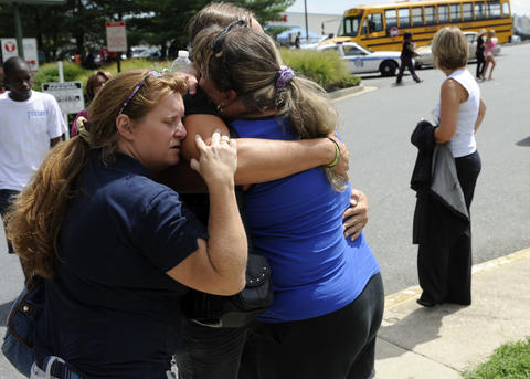 Robin Vitek, left, and Cynthia Rose, right, embrace Nick Vitek, an 11th grader from Perry Hall Middle School. Parents waited for Perry Hall High School students to be released from school after a shooting this morning. They waited along Ebenezer road outside Perry Hall Middle school.