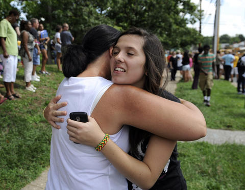 Hannah Hurdle, a junior at Perry Hall HS, is embraced by her mother, Vicky Hurdle, left, as they are reunited this afternoon. Parents waited for Perry Hall High School students to be released from school after a shooting this morning. They waited along Ebenezer road outside Perry Hall Middle school.