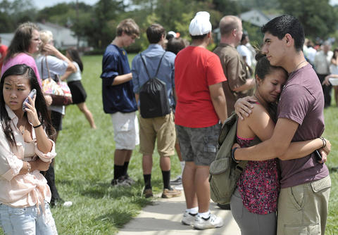 Yoseph Gootee, 16, hugs Hope Yang, 15, following the shooting at Perry Hall High School. He says they practice these drills all the time and is thankful they do.