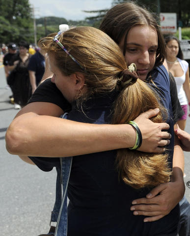 Nick Vitek, an 11th grader at Perry Hall high school, hugs his mom, Robin Vitek, this afternoon on Ebenezer road near the school. There was a shooting this morning in the cafeteria at Perry Hall High School.