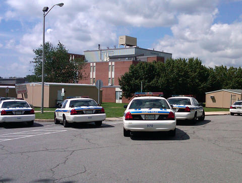 Police cars surround Perry Hall High School following the shooting of a student by another student on the first day of classes. The injured student, whose identity was not revealed, was taken by a Medevac helicopter to University of Maryland 's Shock Trauma Center, where he is in critical condition, authorities said.