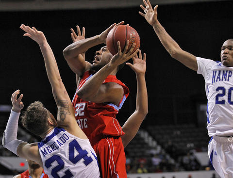 Delaware State University's Marques Oliver, center, looks to the basket around Hampton University's Ramon Mercado, left, and Du'Vaughn Maxwell, right, during Thursday's quarterfinals of the MEAC Tournament.
