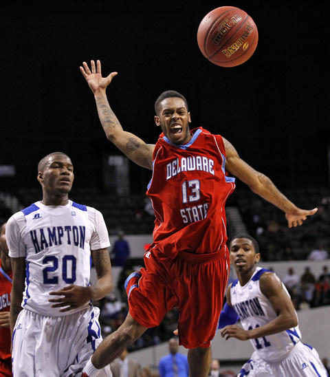 Hampton University's Du'Vaughn Maxwell, left, watches as Delaware State University's Albert Thomas loses control of the ball during Thursday's quarterfinals of the MEAC Tournament.