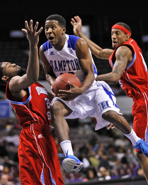 Hampton University's Aaron Austin, center, drives to the basket through Delaware State University's Casey Walker, left, and Tahj Tate during Thursday's quarterfinals of the MEAC Tournament.
