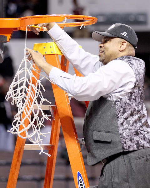 Hampton ladies coach David Six cuts the final string on the net after winning his fourth MEAC tournament championship in a row Saturday after beating Howard 59-38.