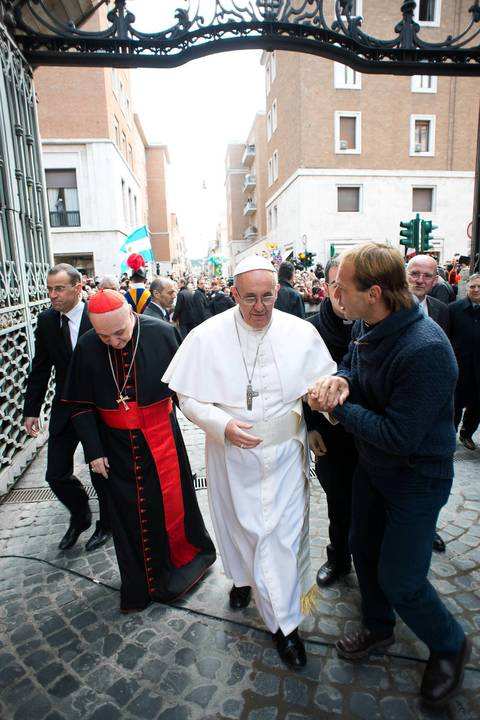 Pope Francis greets a young priest from Uruguay in the street before a mass at Santa Anna church at the Vatican.