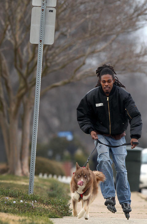 Vincent Johnson III roller-blade's with his dog Kesuk along Chesapeake Ave. in Hampton Thursday evening. This is a nightly activity for the two so the Siberian husky can burn off some energy. No Mags, No Sales, No Internet, No TV