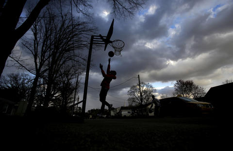 Alton Lassiter, 15, of Newport News plays a game of basketball in the street with friends on Culpepper Avenue Thursday evening as the sun begins to set.