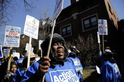 """Daphne Coleman, of Chicago joins Action Now members protesting school closings in front of Chicago Board of Education member David Vitale's house in Chicago. The protesters took their """"School Board Bullies Bus Tour"""" to several board members' homes."""
