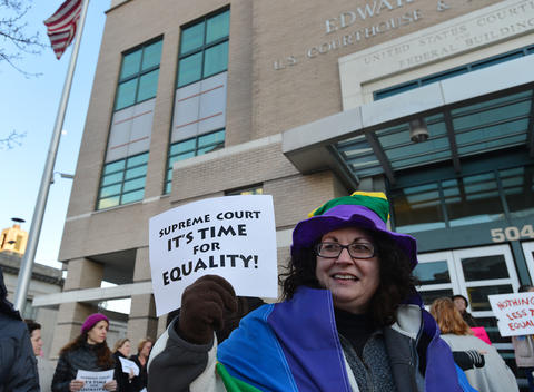 Donna Cruciani, of Allentown holds a sign out towards cars passing on Hamilton street during a candlelight vigil for marriage equality at the Federal Courthouse in Allentown, organized in partnership with Equality Pennsylvania and Eastern PA PFLAG on saturday evening. .