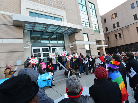 People gather during a candlelight vigil for marriage equality at the Federal Courthouse in Allentown, organized in partnership with Equality Pennsylvania and Eastern PA PFLAG on saturday evening. .