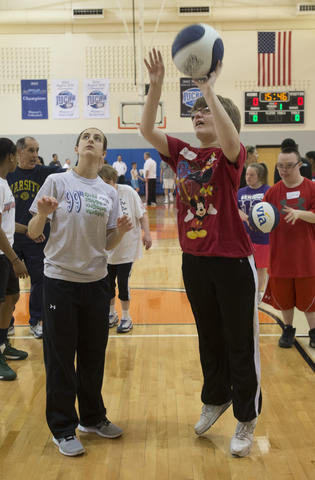 Devon Kotulka, 20, of Wind Gap, shoots a basket while being guided by Salisbury High School basketball player Megan Hrbek, 18, of Salisbury Twp. during the Via All-Star Basketball Clinic for special needs at Northampton Community College on Sunday.