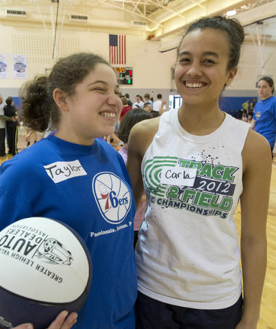 Taylor Bennett, 13, (left) embraces  Wilson High Basketball player Carla Dutt, 17, of Wilson Twp, during the Via All-Star Basketball Clinic for children with special needs at Northampton Community College on Sunday.