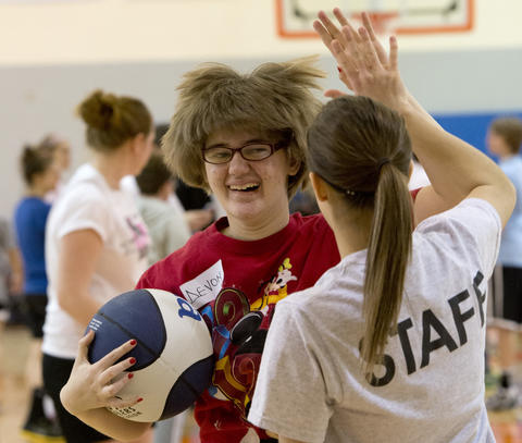 Devon Kotulka, 20, of Wind Gap, gets a high five from Salisbury High School basketball player Megan Hrbek, 18, of Salisbury Twp.  during the Via All-Star Basketball Clinic for special needs at Northampton Community College on Sunday.