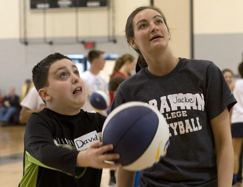 Pius X High School basketball player Jaclyn Smith, 18, of Bangor (right) helps David Weintraub, 12, of Bethlehem.  during the Via All-Star Basketball Clinic for children with special needs at Northampton Community College on Sunday.
