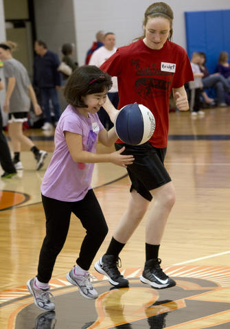 Ayday Gerichten, 11, of Bethlehem, gets encouragement from Bethlehem Catholic High School basketball player Bridget Smith, 18, of Bethlehem, during the Via All-Star Basketball Clinic for special needs at Northampton Community College on Sunday. The clinic focused on the fundamentals of basketball with age specific  handling, passing, and shooting drills.  .///..Harry Fisher / THE MORNING CALL.MC-VIA-ALL-STAR-CLINIC..March 24, 2013...