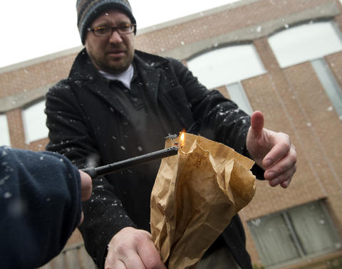 "Rabbi Noam Stein of Memphis, Tennessee lights a fire as he prepares to drop his bag of ""chametz - or leavened food products into a fire, during an annual burning in the rear of Congregation Sons of Israel on Monday's snowy morning. The ritual, which dates to biblical times, is based on the obligation that all Jews have to rid themselves of chametz by the morning before Passover each year."