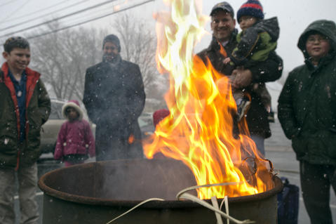 "Rabbi David Wilensky (third from left) oversees the burning of ""chametz - or leavened food products) in the rear of Congregation Sons of Israel on Monday's snowy morning. The ritual, which dates to biblical times, is based on the obligation that all Jews have to rid themselves of chametz by the morning before Passover each year. This year, Passover falls at the earliest date since 1899. For Jews worldwide, Passover is the commemoration of liberation by God, over 3,300 years ago from slavery in Egypt during the time of the Pharaohs. It also celebrates the birth of the Jewish nation under the leadership of Moses. Passover commences on the 15th of the Hebrew month of Nisan and lasts for 8 days (7 in Israel)."