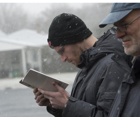 Allentown native Ari Blinder (left) of Highland Park, New Jersey recites the declaration that he has rid his household of all chametz (leavened food products) during an annual burning in the rear of Congregation Sons of Israel on Monday's snowy morning.