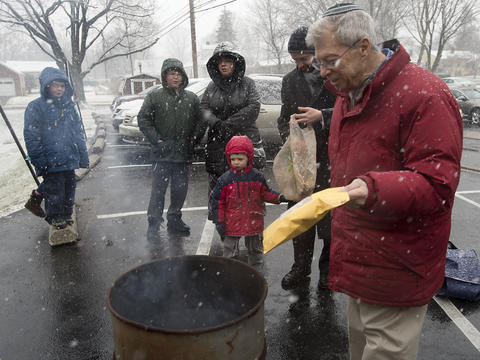 "Michael Notis of Allentown (far right) places an envelope contaning his ""chametz - or leavened food products) during an annual burning in the rear of Congregation Sons of Israel on Monday's snowy morning. The ritual, which dates to biblical times, is based on the obligation that all Jews have to rid themselves of chametz by the morning before Passover each year. This year, Passover falls at the earliest date since 1899. For Jews worldwide, Passover is the commemoration of liberation by God, over 3,300 years ago from slavery in Egypt during the time of the Pharaohs."