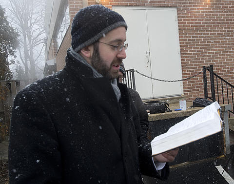 "Rabbi David Wilensky reads a blessing during the burning of ""chametz - or leavened food products) in the rear of Congregation Sons of Israel on Monday's snowy morning. The ritual, which dates to biblical times, is based on the obligation that all Jews have to rid themselves of chametz by the morning before Passover each year. This year, Passover falls at the earliest date since 1899. For Jews worldwide, Passover is the commemoration of liberation by God, over 3,300 years ago from slavery in Egypt during the time of the Pharaohs. It also celebrates the birth of the Jewish nation under the leadership of Moses. Passover commences on the 15th of the Hebrew month of Nisan and lasts for 8 days (7 in Israel)."
