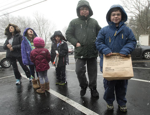 "Yitzi Powers, 11, of Allentown (second from right) and brother Ari, 8, arrive with their bag of ""chametz - or leavened food products) to be burned in the rear of Congregation Sons of Israel on Monday's snowy morning."