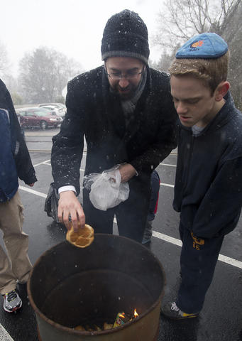 "Asher Stein, 13, of Memphis, Tennessee (right) watches as Rabbi David Wilensky places baked goods (a form of ""chametz - or leavened food products) into a fire during an annual burning in the rear of Congregation Sons of Israel on Monday's snowy morning. The ritual, which dates to biblical times, is based on the obligation that all Jews have to rid themselves of chametz by the morning before Passover each year. This year, Passover falls at the earliest date since 1899. For Jews worldwide, Passover is the commemoration of liberation by God, over 3,300 years ago from slavery in Egypt during the time of the Pharaohs. It also celebrates the birth of the Jewish nation under the leadership of Moses. Passover commences on the 15th of the Hebrew month of Nisan and lasts for 8 days (7 in Israel)."