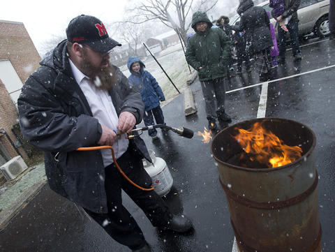 "Jonathan Powers of Allentown uses a torch to facilitate the burning of ""chametz - or leavened food products) in the rear of Congregation Sons of Israel on Monday's snowy morning. The ritual, which dates to biblical times, is based on the obligation that all Jews have to rid themselves of chametz by the morning before Passover each year. This year, Passover falls at the earliest date since 1899. For Jews worldwide, Passover is the commemoration of liberation by God, over 3,300 years ago from slavery in Egypt during the time of the Pharaohs. It also celebrates the birth of the Jewish nation under the leadership of Moses. Passover commences on the 15th of the Hebrew month of Nisan and lasts for 8 days (7 in Israel)."